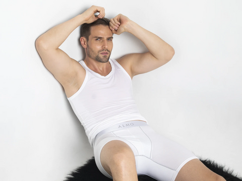 man resting his back against a white colored wall while wearing a white colored vest and white colored underwear