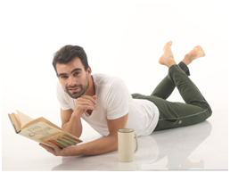 man reading book and lying on ground wearing white almo t-shirt and rifle green trackpants