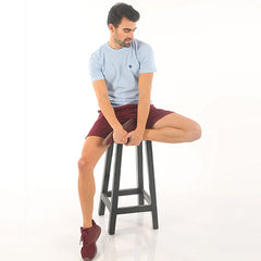 man in red shorts sitting on a stool