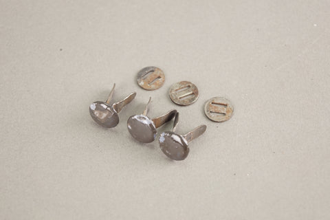 Set of three helmet rivets.