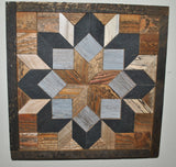 Center wood star surrounded by gray squares and black diamonds to create a flower design that is bordered in dark colored barn wood.