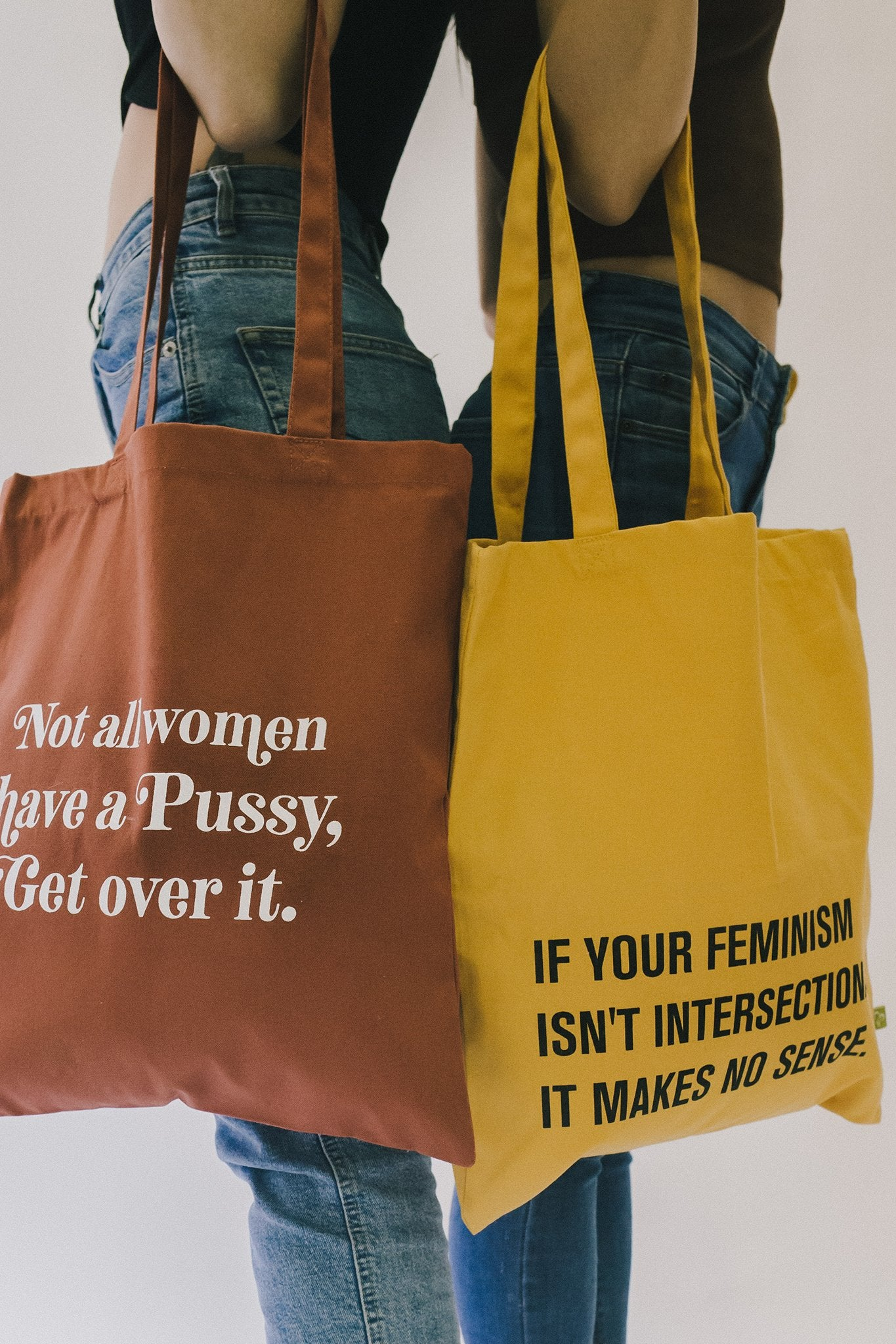 "Two women standing back to back with blue jeans and brown tee shirts. The women on the left is holding a burnt orange tote bag with white ""Not all women have a pussy, get over it"" print on it. The women on the right is holding a yellow tote bag with black ""If your feminism isn't intersectional it makes no sense"" print on it."