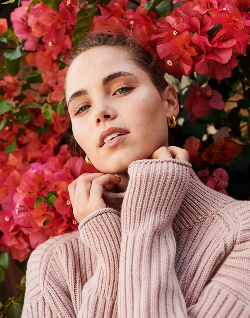 Emma wears the Lou Ribbed Turtleneck in Pink