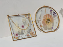 Load image into Gallery viewer, Wildflower Pressed Flower Frame - Gold Circle A gorgeous selection of dried and hand-pressed florals in pinks, purples, lilacs and warm white tones. Featuring seasonal flowers such as hydrangea, ferns, poppies, statice, violets, pansies and lunaria. Perfect for decorating a living area, bedroom, childs' nursery, playroom or hallway space Makes a lovely gift option also! Can be hung by the delicate gold chain or leant upright on a shelf Glass frame