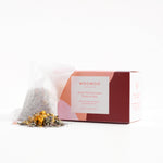 white sachet of herbal bathing tisane with a small pile of loose herbs in front. product package on the right