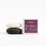 white cleansing sponge on top of a black cleansing sponge with the white square package on the right hand side