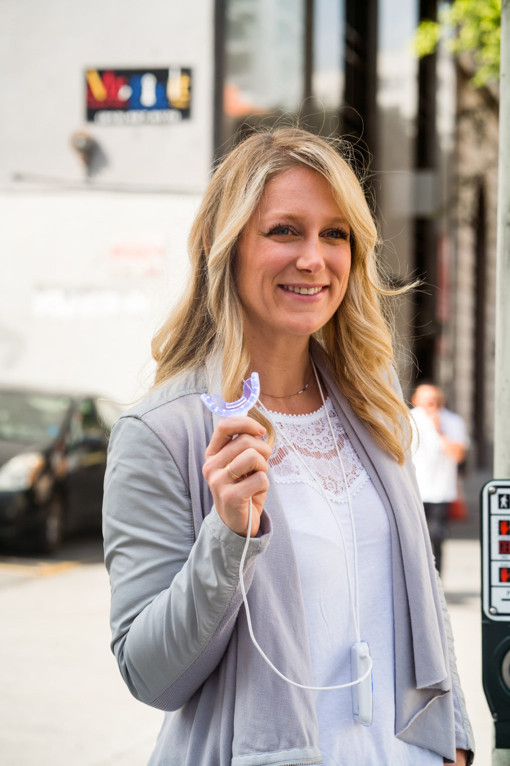 Smiling woman standing at an intersection holding the GLO Science at-home teeth whitening system.