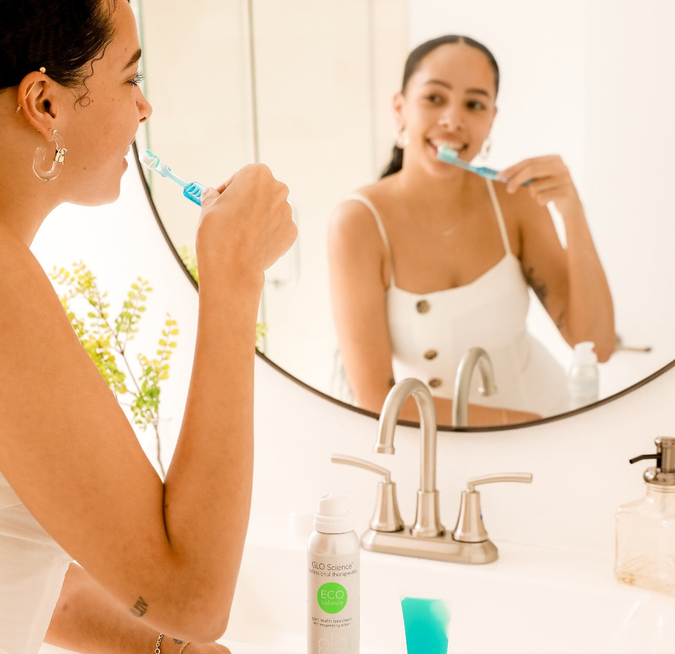 Smiling woman brushing her teeth in front of a bathroom mirror and a GLO Science product bottle.