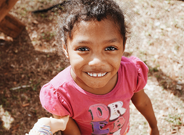 Little girl with dark eyes and a pink T-shirt looking up at the camera and smiling with her teeth showing.