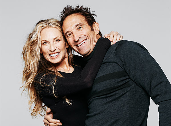 Dr. Jonathan B. Levine and Stacey Levine smiling and embracing in front of a light gray background.
