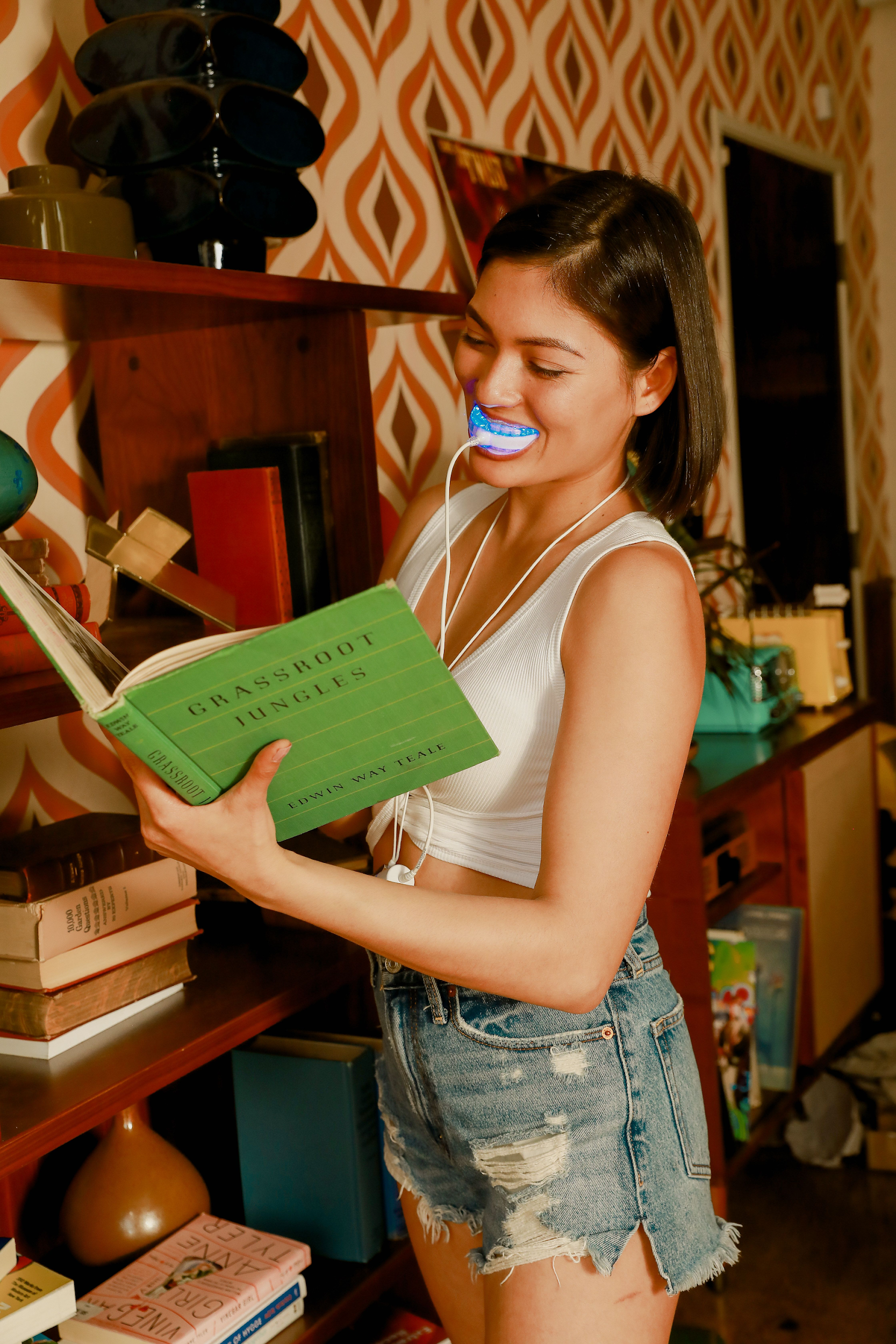 Young woman in shorts using a GLO Science teeth whitening device while standing next to a bookshelf reading Grassroot Jungles.
