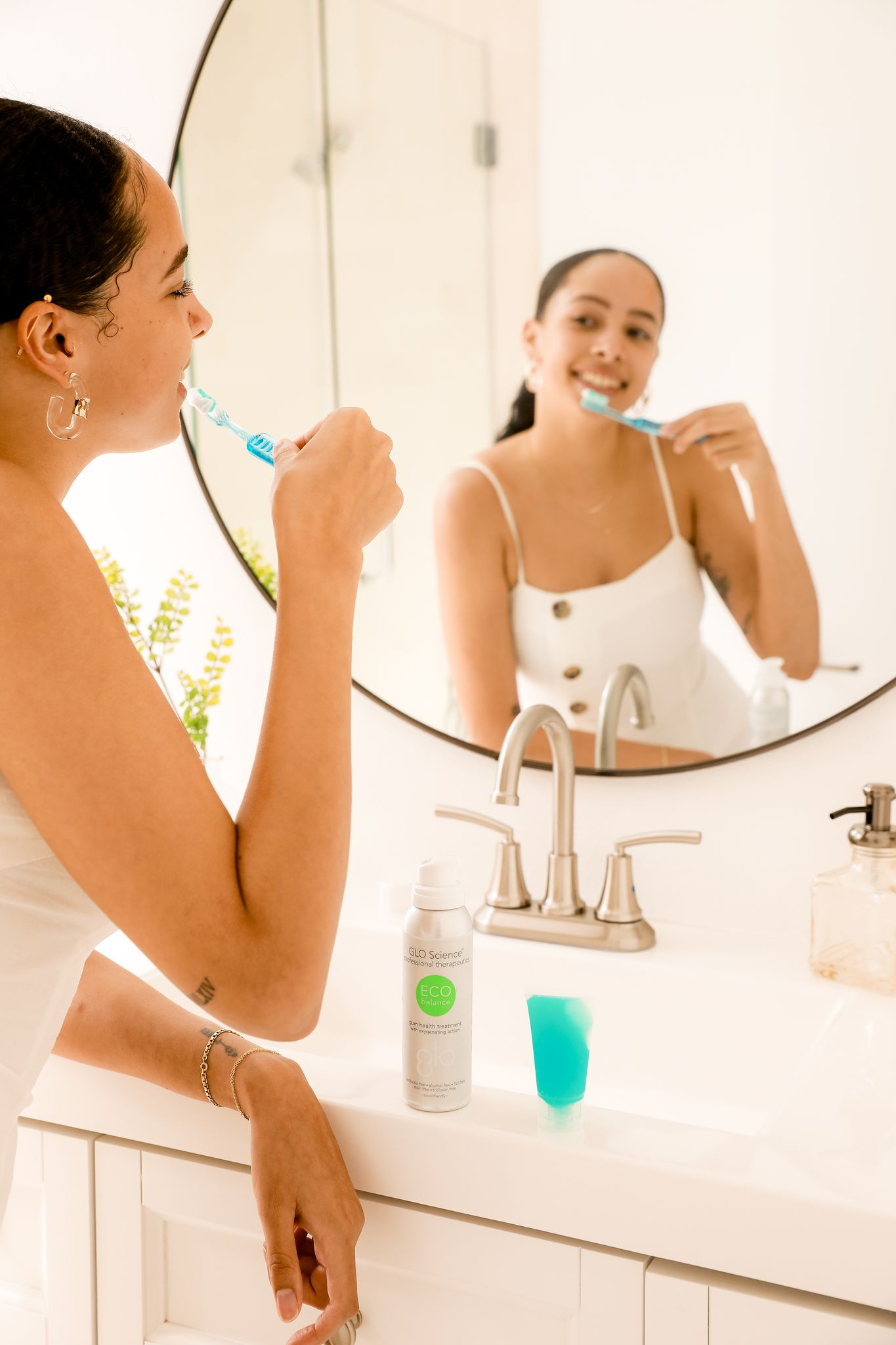 Smiling woman brushing her teeth in front of a mirror with a bottle of Eco Balance Oral Health Booster.