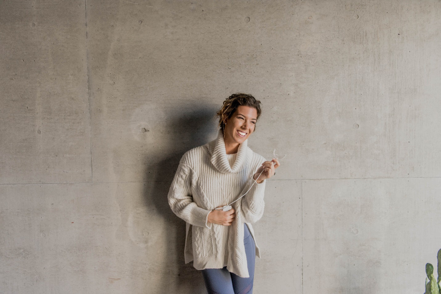 Smiling woman in an oversized sweater standing against a concrete wall while holding a GLO Brilliant teeth whitening device.