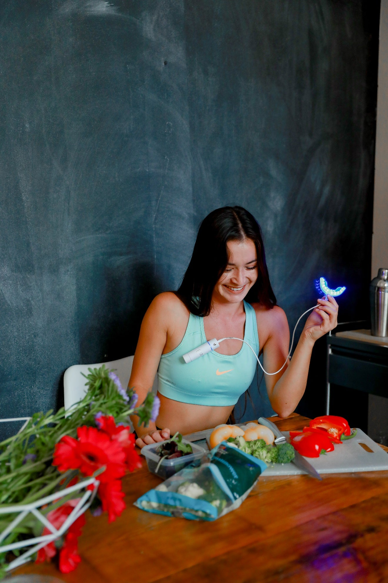Smiling woman wearing athletic clothing sitting at table chopping vegetables and holding a GLO Lit teeth whitening device.