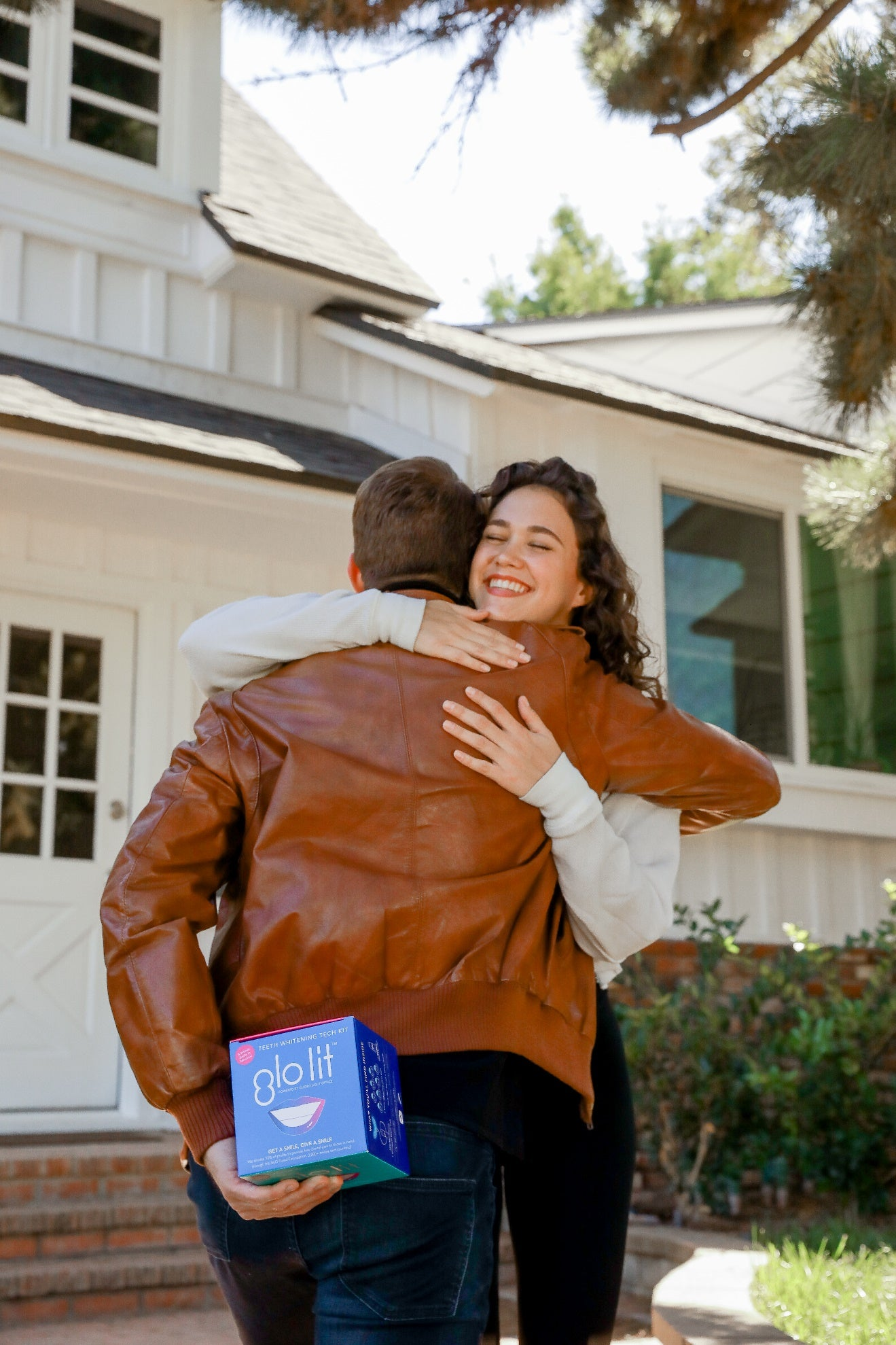 Man and woman hugging in front of a house while the man holds a GLO Lit teeth whitening system box behind his back.