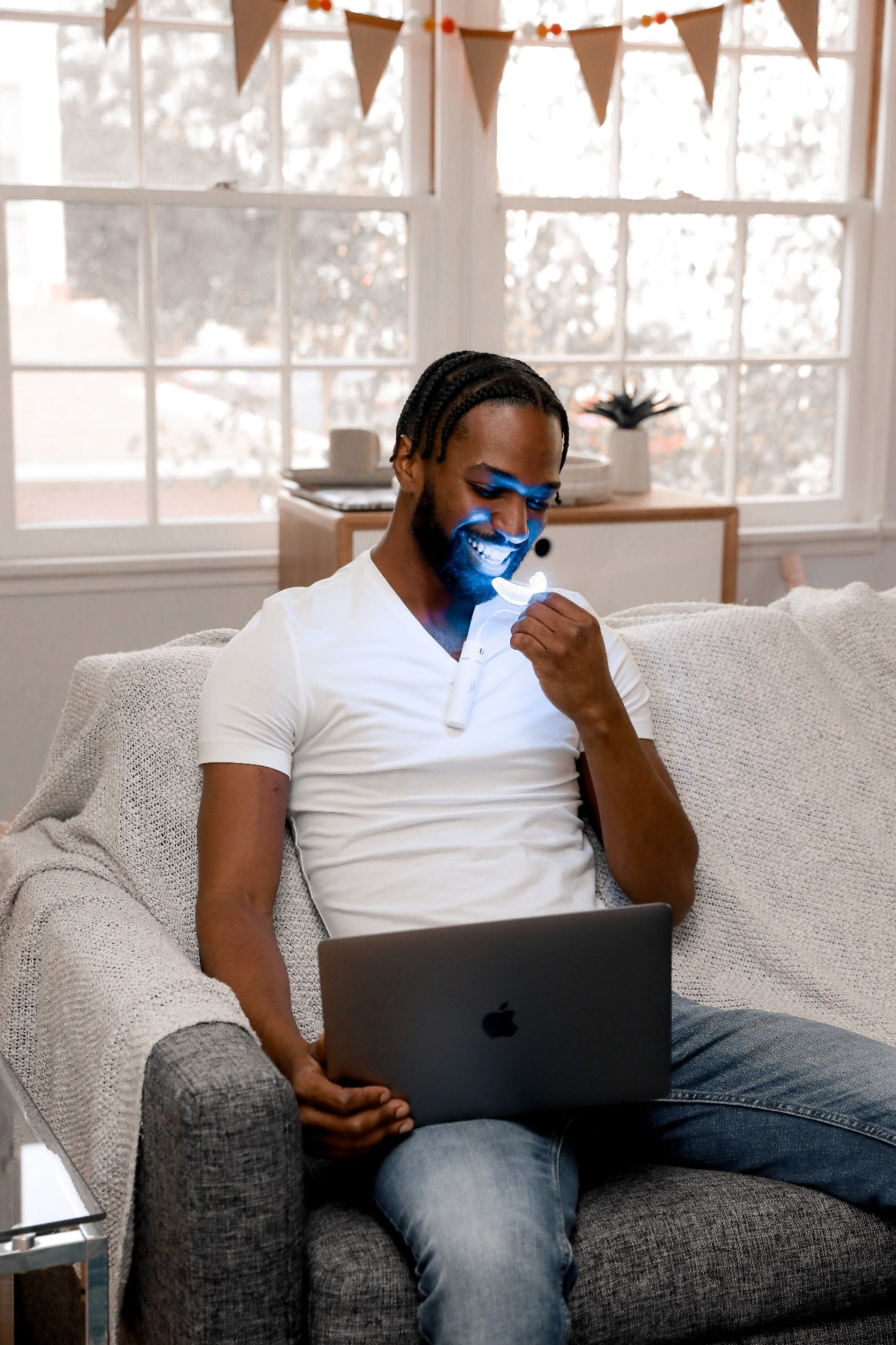 A person with a mask on his face sitting on a couch with a computer