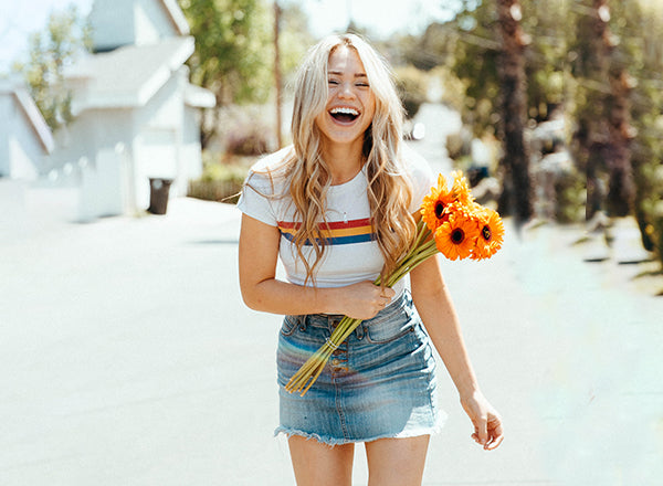 Young woman wearing a skirt, smiling and laughing outside while holding a bouquet of orange flowers.