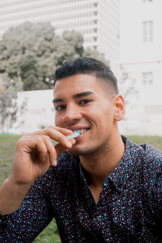 Smiling young man sitting outside while he applies a GLO Vial to his teeth.