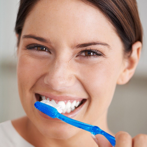 Smiling woman with brown hair and brown eyes brushing her teeth with a blue toothbrush.
