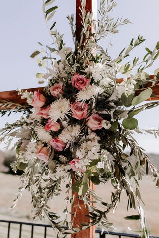White and pink flower installation on a cross.