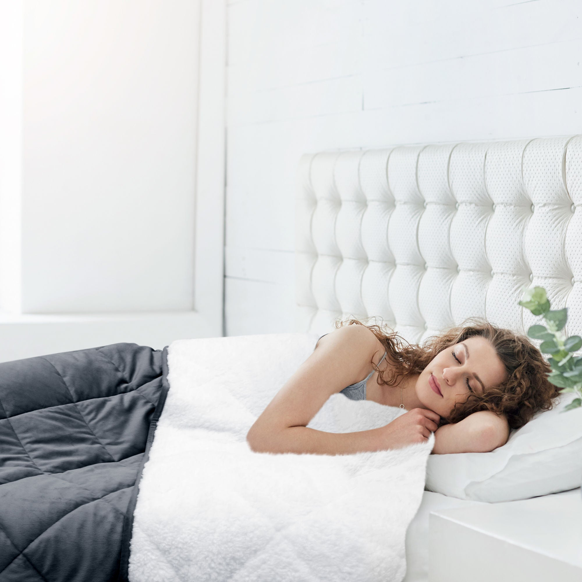 Photograph of a young woman laying in bed in deep sleep using a sherpa and fleece weighted blanket from Restasy