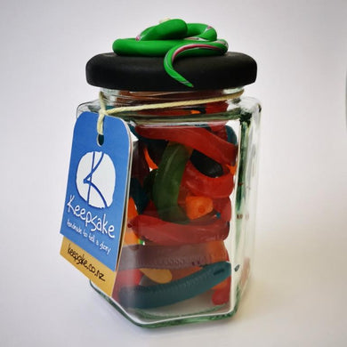 270ml glass hexagonal lolly jar hand-decorated in New Zealand, with  an air-tight lid decorated with a  polymer clay snake. Filled with snake lollies
