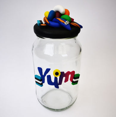 Extra-large glass treat jar hand-decorated in New Zealand, with an air-tight lid decorated with colourful polymer clay licorice allsorts, jelly beans and a blue snake, and with polymer clay YUM on the side. Perfect for the whole family or as a gift for Nana or Granddad.