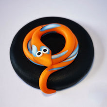 Load image into Gallery viewer, 270ml glass hexagonal lolly jar hand-decorated in New Zealand, with  an air-tight lid decorated with a orange polymer clay snake. Filled with snake lollies