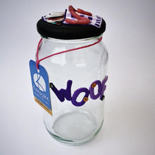 Load image into Gallery viewer, Round Dog glass treat Jar hand-decorated in New Zealand,  with  purple WOOF on the front and a polymer clay decorated air-tight lid, including a purple tablecloth, miniture sausages and steak as a gift for that special dog