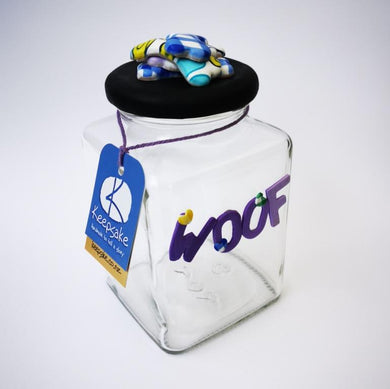Square Dog glass treat Jar hand-decorated in New Zealand,  with a pile of  funky brightly decorated polymer clay bones on the air-tight lid, ideal as a gift for that special dog
