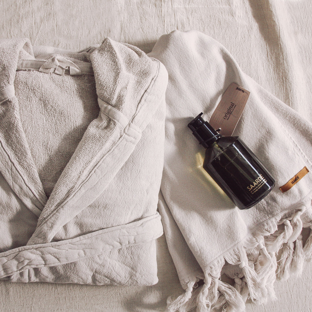 Clay coloured hooded cotton robe with matching hand towel and liquid wash in a glass bottle