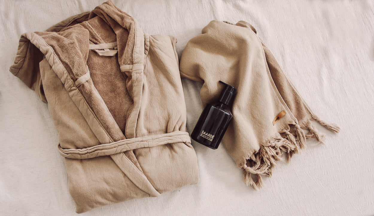 Nutmeg coloured hooded cotton robe with matching hand towel and liquid wash in a glass bottle