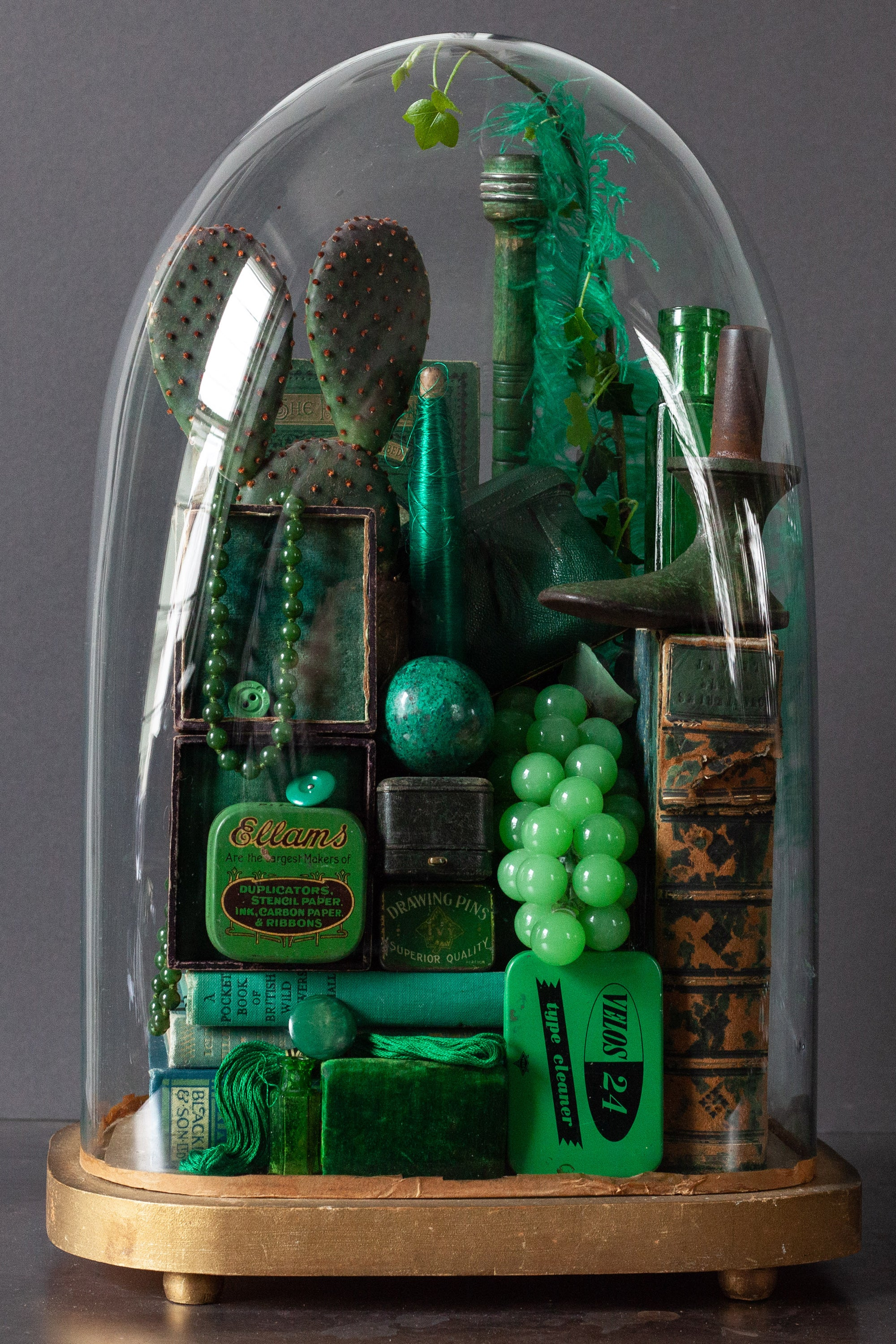 Collection of green vintage curiosities in glass dome