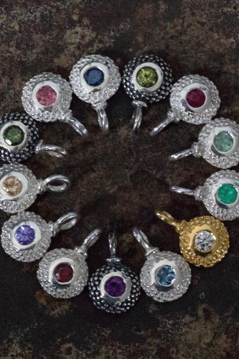 Close up of a circular set of bobbled pollen birthstone charms.