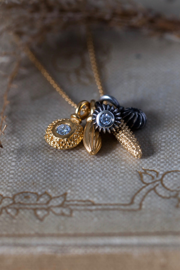A dainty pendant featuring a cluster of five delicate gold plated silver and oxidised silver pollen charms on a fine trace gold plated silver chain, including three set with April's birthstone Cubic Zirconia.