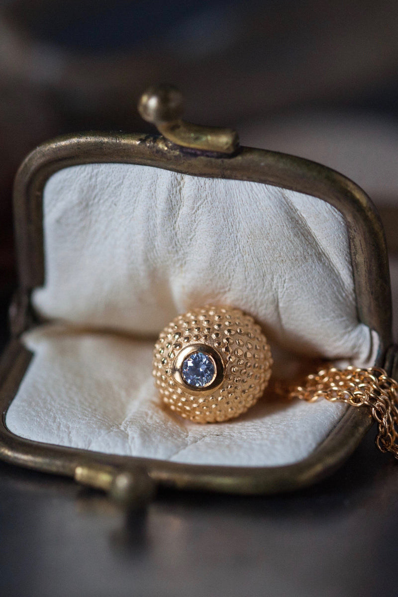 A special birthstone pendant in yellow gold plated silver for April – its centrepiece is a tactile textured ball with a glistening Diamond at the base.