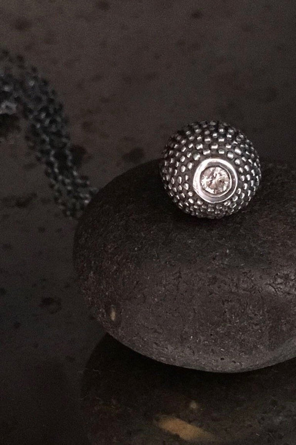 A special birthstone pendant in oxidised silver for April – its centrepiece is a tactile textured ball with a glistening Diamond at the base.