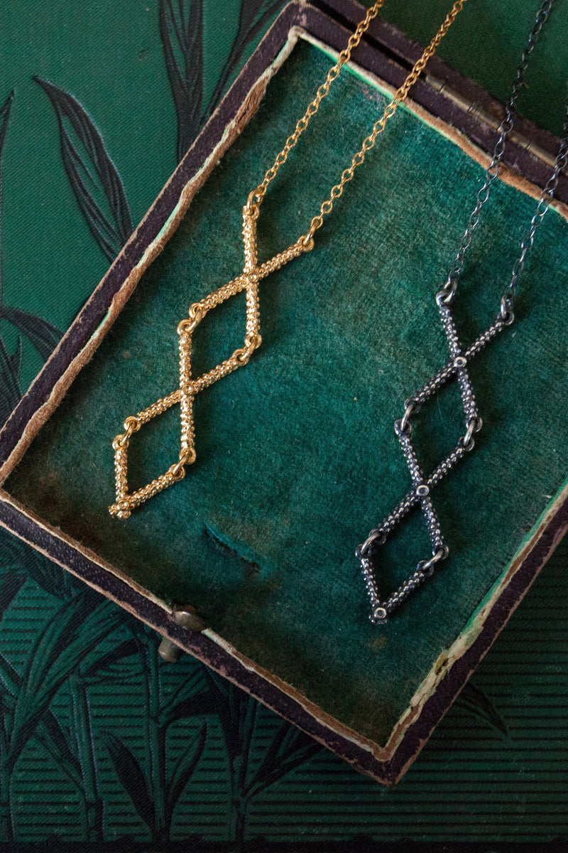 My Kiss Cross Necklace in gold plated silver and oxidised silver is formed from linked crosses or kisses