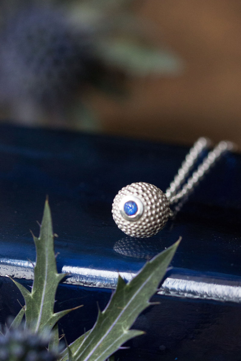A birthstone pendant for September – a tactile textured ball with a glistening blue Sapphire at the base