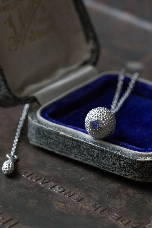 A special birthstone pendant for December in a jewellery box – its centrepiece is a tactile textured ball with a glistening Tanzanite at the base.