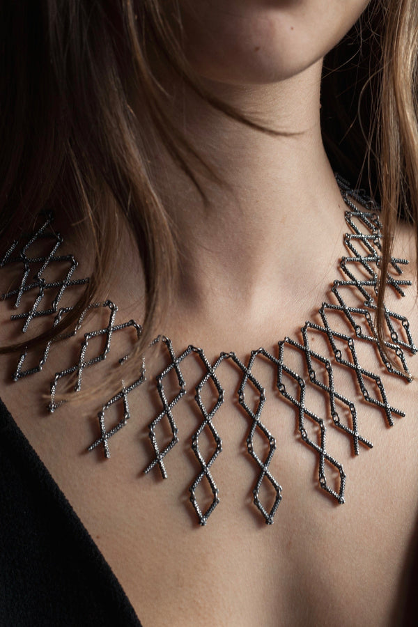 Kiss Cross collar style necklace worn by a model in oxidised silver made from interlocking cross shaped links