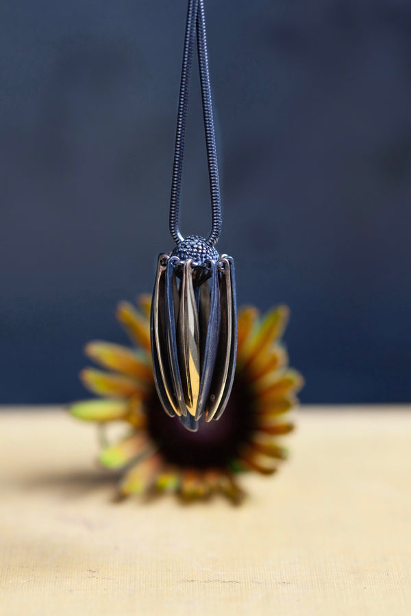 My Aster Pendant Necklace hangs like a tassel with its bobbled head fringed with a series of long elegant flowing petals that twirl pleasingly to create elegant movement and interest.