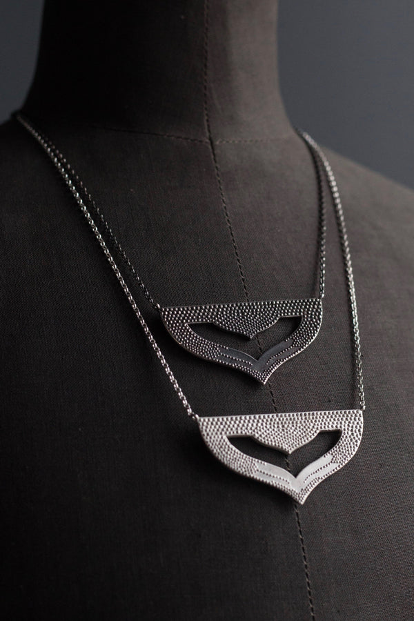 A pair of my Astral Pendant Necklaces, inspired by Asian warrior helmets and the necklace I created for the Star Wars film, Solo. This stylish pendant features my signature texture to catch the light and can be worn at two lengths.