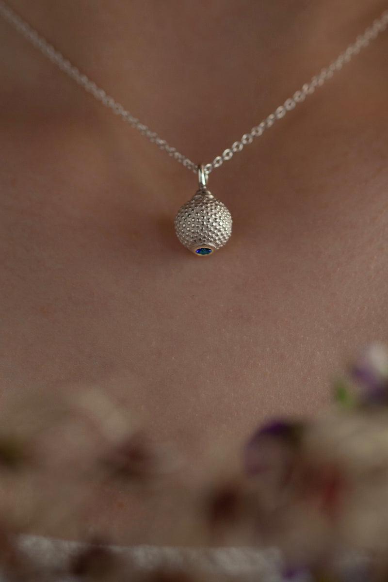 A birthstone pendant for November worn by a model – a tactile textured ball with a Swiss Blue Topaz