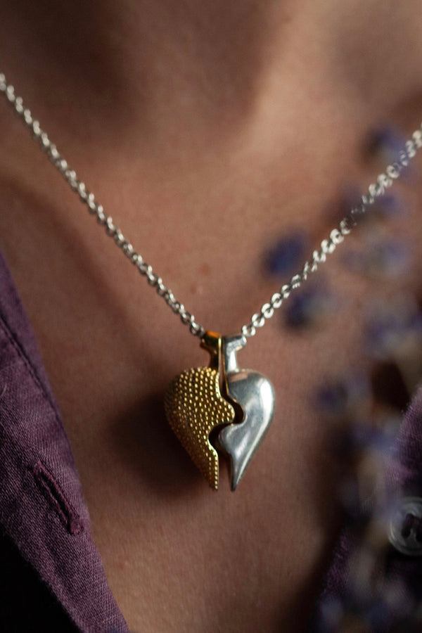 Chunky heart shaped pendant worn in silver and gold plated silverin two separate halves that together make one