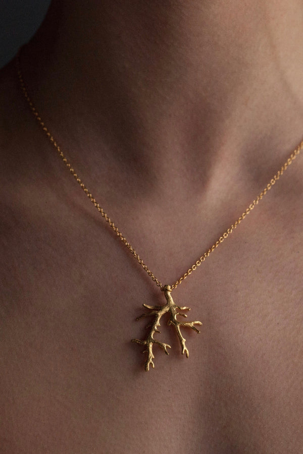 My Branch Pendant Necklace worn by a model in yellow gold plated silver, inspired by my love of trees, sits beautifully against the skin or clothing and makes the everyday a bit more special
