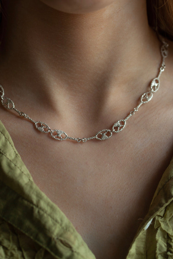 My Fishermans Knot Necklace worn by a model is formed from a series of links with a motif inspired by the intricate knotting techniques used for nets in the past