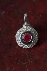 A bobbled pollen charm in silver with a ravishing ruby, July's birthstone.