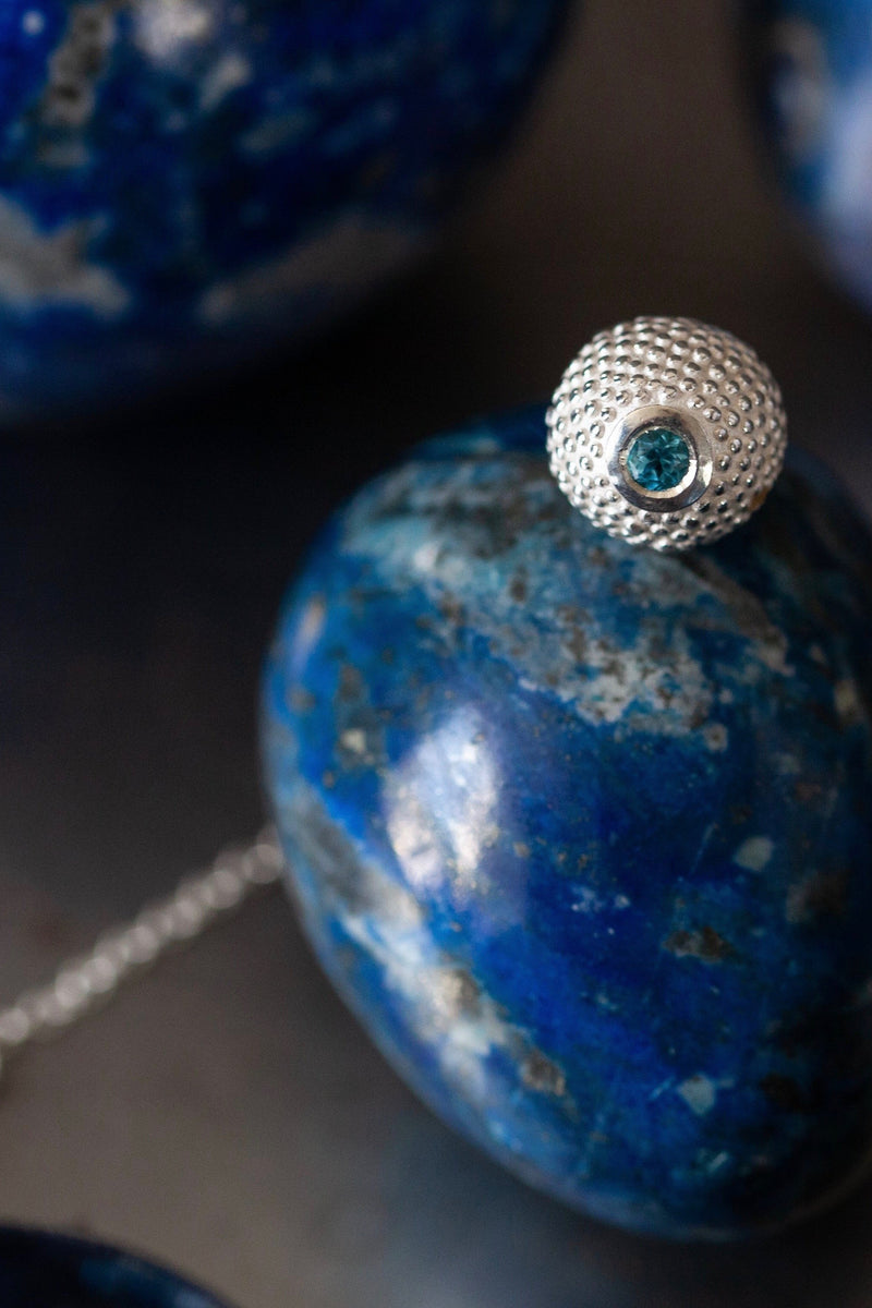 A birthstone pendant for November – a tactile textured ball with a glistening Swiss Blue Topaz at the base