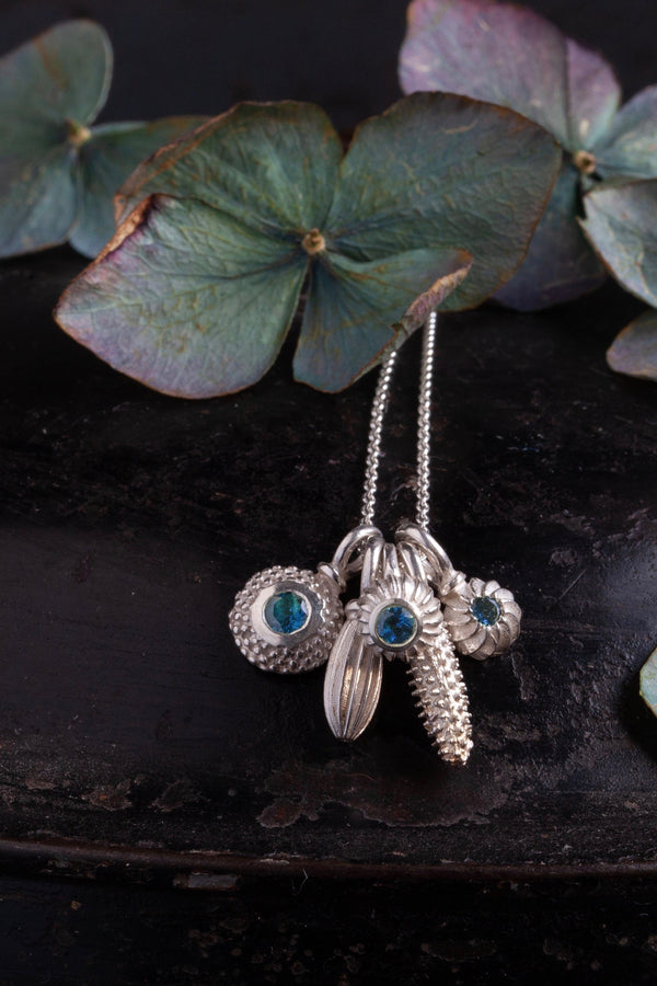 A dainty pendant with a cluster of 5 silver pollen charms 3 set with a Blue Tourmaline October's birthstone
